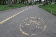 Percorso della bici nel parco: segno sull'asfalto Immagine Stock Libera da Diritti