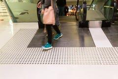 Percorso di pavimentazione tattile per l'uscita cieca dell'entrata della scala mobile fotografia stock