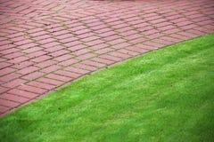 Percorso di pietra del giardino con erba, marciapiede del mattone Immagine Stock Libera da Diritti