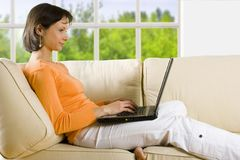 PERCORSO DI RESIDUO DELLA POTATURA MECCANICA! Donna con il computer portatile sul sofà Fotografia Stock