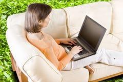 PERCORSO DI RESIDUO DELLA POTATURA MECCANICA! Donna con il computer portatile sul sofà immagine stock libera da diritti