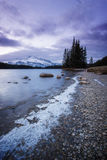 Percorso ghiacciato lungo il lago che conduce alla piccola isola con gli alberi e l'alta montagna innevata dietro, PA nazionale d Immagine Stock