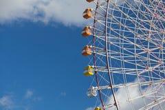 Percorso gigante della luna park della ruota contro cielo blu Immagine Stock