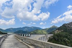 Percorso & montagne curvi della diga sotto le nuvole fotografia stock