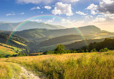 Percorso sul prato del pendio di collina in montagna ad alba Fotografia Stock Libera da Diritti