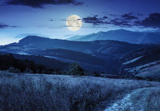 Percorso sul prato del pendio di collina in montagna alla notte Immagini Stock