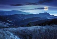 Percorso sul prato del pendio di collina in montagna alla notte Immagine Stock