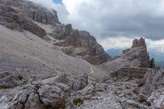Percorso vicino ai massi giganti in un paesaggio scuro e nuvoloso della montagna immagine stock libera da diritti