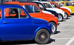 A row of colorful Fiat 500s  in a roadside parking lot, waiting to participate in an auto gathering later. Percoto, Italy. March 24 2019. A row of colorful Fiat royalty free stock photo