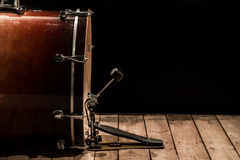 Percussion instrument, bass drum with pedal on wooden boards with a black background. The music concept Royalty Free Stock Photo