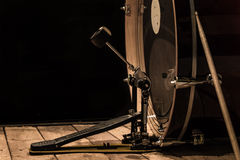 Percussion instrument, bass drum with pedal on wooden boards with a black background. The music concept Royalty Free Stock Photos