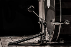 Percussion instrument, bass drum with pedal on wooden boards with a black background. The music concept Stock Photography