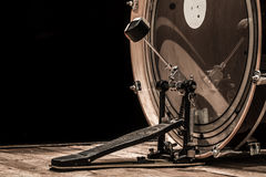 Percussion instrument, bass drum with pedal on wooden boards with a black background. The music concept Royalty Free Stock Image