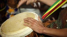 Percussione africana - musica tradizionale Primo piano delle mani dell'uomo che espellono un battito di un su un djembe coperto d stock footage