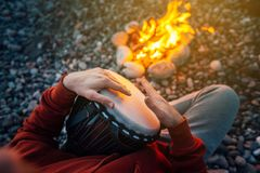 Percussionist playing djembe sitting by fire, close-up. Percussionist playing djembe sitting by the fire, close-up royalty free stock photos