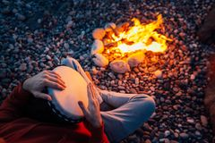 Percussionist playing djembe sitting by fire, close-up. Percussionist playing djembe sitting by the fire, close-up stock photo