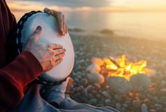 Percussionist plays djembe on the seashore near fire, hands close up. Percussionist plays djembe on the seashore near the fire, hands close up royalty free stock photography