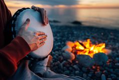 Percussionist plays djembe on the seashore near fire, hands close up. Percussionist plays djembe on the seashore near the fire, hands close up stock images