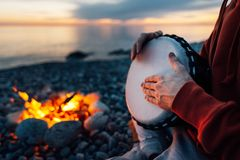 Percussionist plays djembe on the seashore near fire, hands close up. Percussionist plays djembe on the seashore near the fire, hands close up stock image