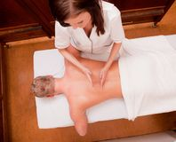 Percussive Massage. A man receiving a percussive back massage at an old style spa Stock Photography