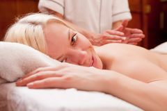 Percussive Massage. A blond female looking at the camera, receiving a percussive back massage in a spa Royalty Free Stock Photo