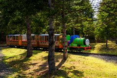 Percy steamy engine in Thomas land. Yamanashi, Japan - May 01, 2017: Percy steamy engine train running on railway in evening at Thomas land in Fuji-Q Highland stock images