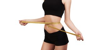 Perda de peso, corpo magro, conceito saudável do estilo de vida Menina da aptidão que mede sua cintura com medida da fita, isolad imagens de stock royalty free
