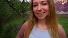 perdez vers le haut du visage de la fille de sourire près du bois de cèdre en parc, mouvement lent clips vidéos