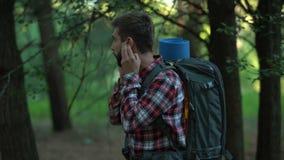 Perdido en el campista masculino de maderas que intenta llamar 911, conexión pobre, tecnologías metrajes