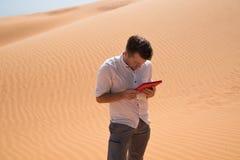 Perdido en el desierto Hombre caucásico que se sienta en la arena con la tableta Él es perdido y de mirada en mapa adonde ir Fotos de archivo libres de regalías