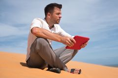 Perdido en el desierto Hombre caucásico que se sienta en la arena con la tableta Él es perdido y lookking en mapa adonde ir Fotos de archivo libres de regalías