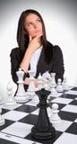 Perdido na mulher do pensamento que olha acima Tabuleiro de xadrez com Imagem de Stock Royalty Free