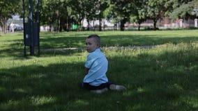 Perdieron al pequeño muchacho triste en la camisa azul en el parque y sentarse en la hierba solamente almacen de video