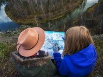 Perdieron a las muchachas en las montañas cerca de un río hermoso foto de archivo