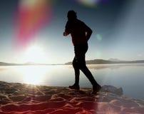 Perdita di luce nella lente Esercizio esile alto dell'uomo sulla spiaggia del lago della montagna Fotografia Stock Libera da Diritti