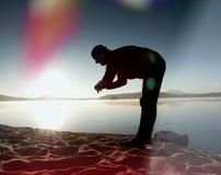 Perdita di luce nella lente Esercizio esile alto dell'uomo sulla spiaggia del lago della montagna Immagini Stock