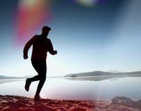 Perdita di luce nella lente Uomo corrente Funzionamento dello sportivo, tipo pareggiante durante l'alba sopra la spiaggia sabbios Immagini Stock