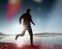 Perdita di luce nella lente Uomo corrente Funzionamento dello sportivo, tipo pareggiante durante l'alba sopra la spiaggia sabbios Fotografia Stock