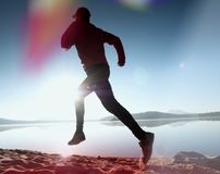 Perdita di luce nella lente Uomo corrente Funzionamento dello sportivo, tipo pareggiante durante l'alba sopra la spiaggia sabbios Immagine Stock