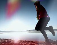 Perdita di luce nella lente Uomo corrente Funzionamento dello sportivo, tipo pareggiante durante l'alba sopra la spiaggia sabbios Immagini Stock Libere da Diritti