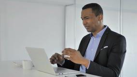 Perdita, uomo d'affari afroamericano casuale frustrato Working sul computer portatile video d archivio