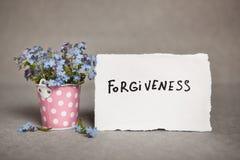 Perdono - testo su carta reale bianca con i fiori blu fotografia stock