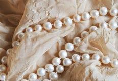 Perełkowi koraliki na beż drapującym tkaniny tle Fotografia Stock