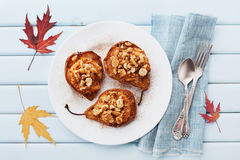 Pere al forno con la ricotta, le noci, il miele e la cannella in piatto su una tavola d'annata blu da sopra Dessert delizioso di  Immagini Stock Libere da Diritti