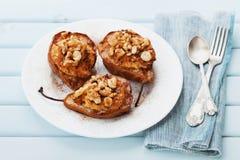 Pere al forno con la ricotta, le noci, il miele e la cannella in un piatto bianco su una tavola d'annata blu Dessert delizioso di Fotografie Stock Libere da Diritti