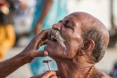 Peregrino que consigue un afeitado áspero en el Kumbha Mela, la India Fotografía de archivo