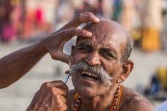 Peregrino que consigue un afeitado áspero en el Kumbha Mela, la India Fotos de archivo libres de regalías