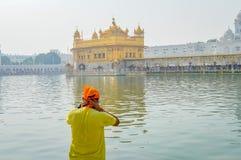 Peregrino sikh que ruega en el tanque santo cerca del templo de oro Sri Harmandir Sahib, Amritsar, la INDIA imagenes de archivo
