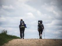 Peregrinos en el camino debajo de las nubes imagen de archivo libre de regalías