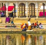 Peregrinos en un Ghat de baño en el lago santo Pushkar Foto de archivo libre de regalías